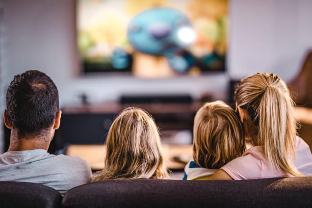 vista trasera de una familia viendo tv en el sofá en casa. - family watching tv fotografías e imágenes de stock