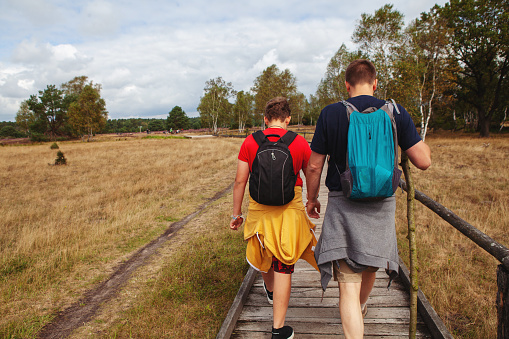 Rear view of a father and his son walking on a wooden footpath on their hiking trip with their backpacks on