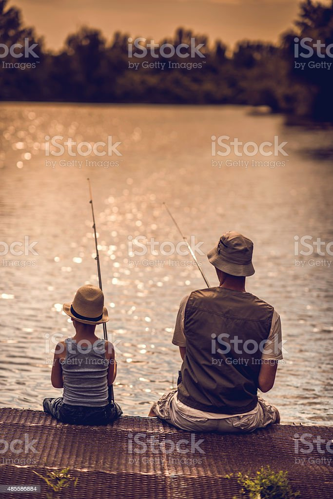 Rear view of a father and son fishing in freshwaters. stock photo