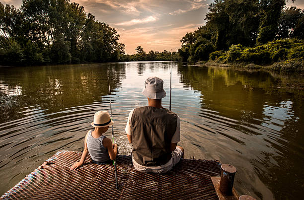 Rear view of a father and son fishing. stock photo