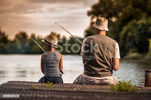 992209122 istock photo Rear view of a father and son freshwater fishing. 489663526