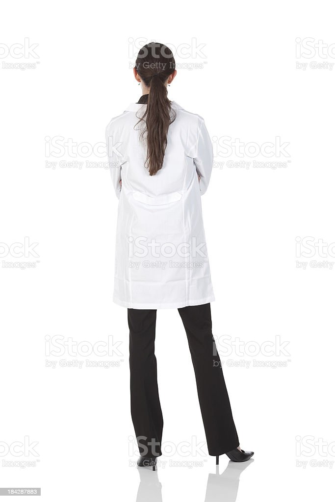 Rear view of a female doctor standing with arms crossed stock photo
