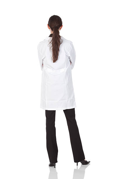 rear view of a female doctor standing with arms crossed - laboratory coat stock photos and pictures