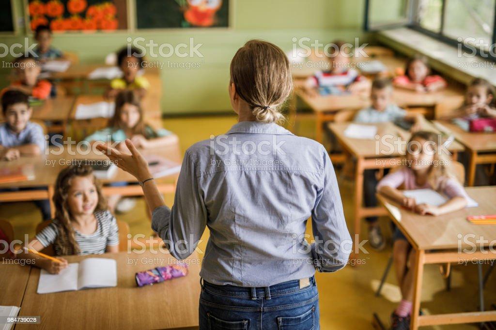 Heckansicht des einen weiblichen Volksschullehrer eine Lektion im Unterricht zu geben. Lizenzfreies stock-foto