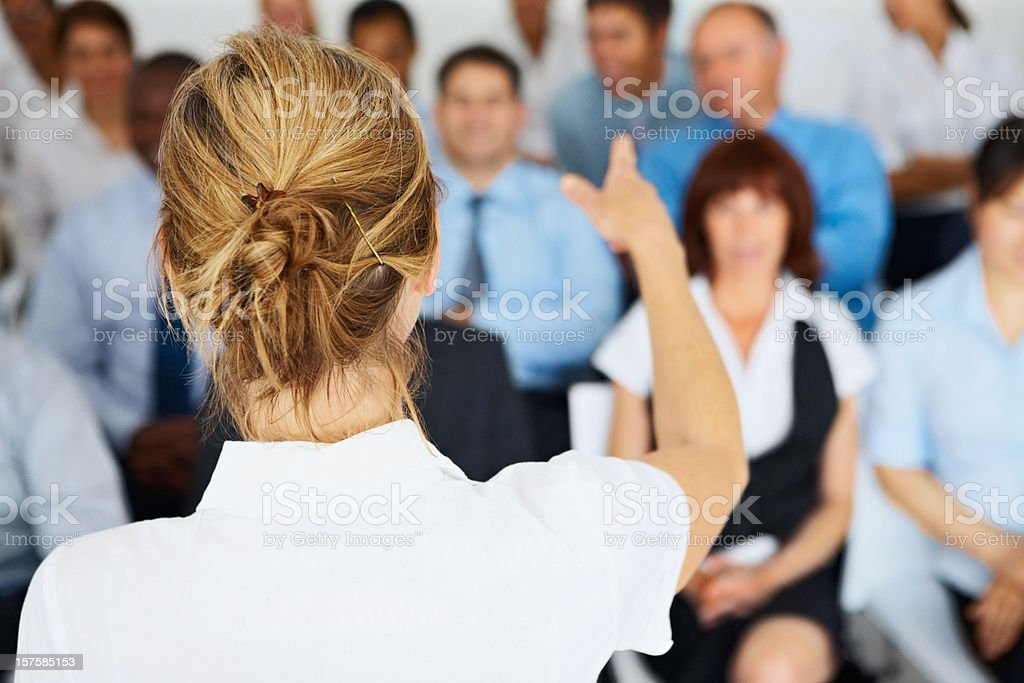 Rear view of a female speaker giving presentation to team stock photo