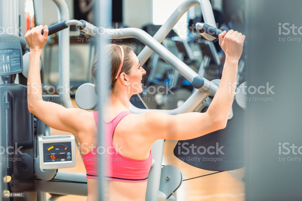Rear view of a fit woman with toned arms and back exercising at the gym - Royalty-free Adult Stock Photo