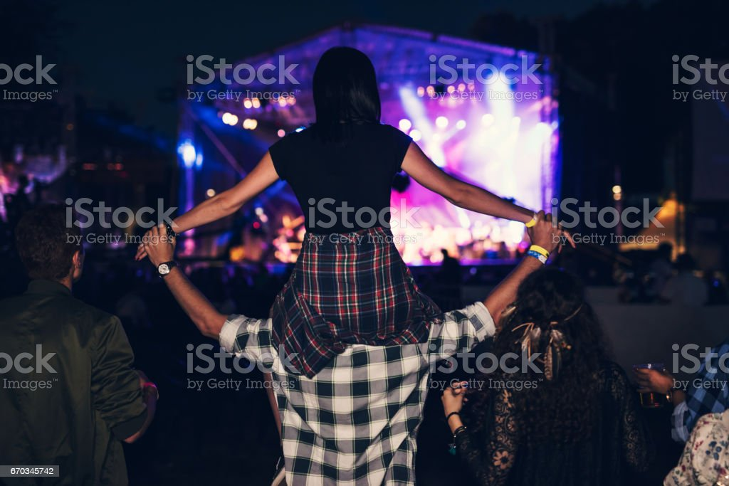 Rear view of a girl getting carried on a friends shoulders at the music festival. stock photo
