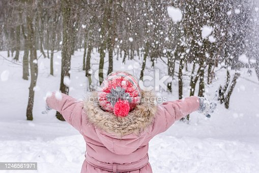 A rear view of a girl looking upwards at the snow in a sunny winter day, at the tree background.