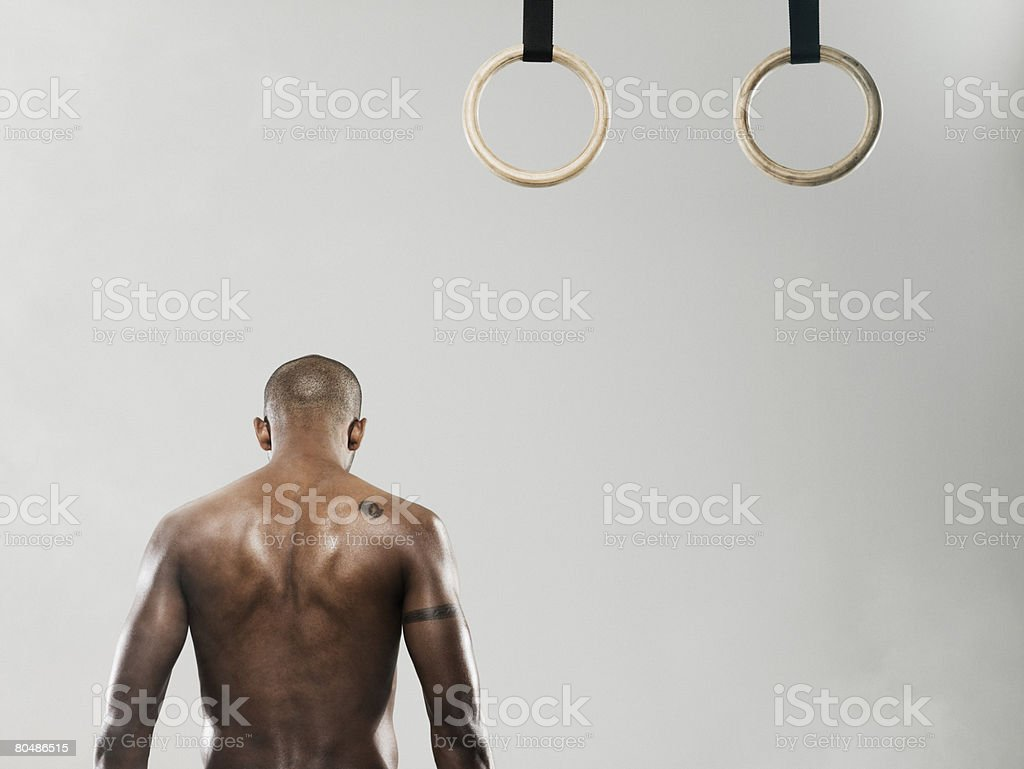 Rear view of a gymnast and gymnastic rings royalty-free stock photo