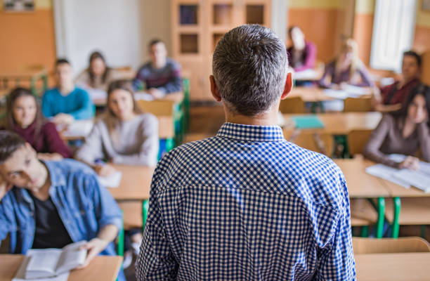 Rear view of a high school teacher giving a lecture. Back view of male professor giving lecture to high school students in the classroom. high school building stock pictures, royalty-free photos & images