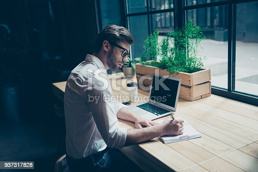 937328186 istock photo Rear view of a journalist stylish guy writing a story in a workplace in loft styled coworking, well dressed, in glasses 937317828