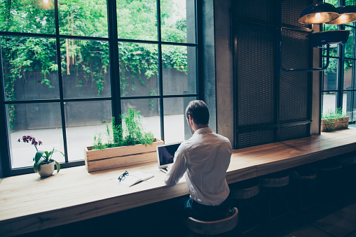 istock Rear view of a journalist stylish guy writing a story in a workplace in loft styled coworking, well dressed, sitting near window with view of garden 937328186