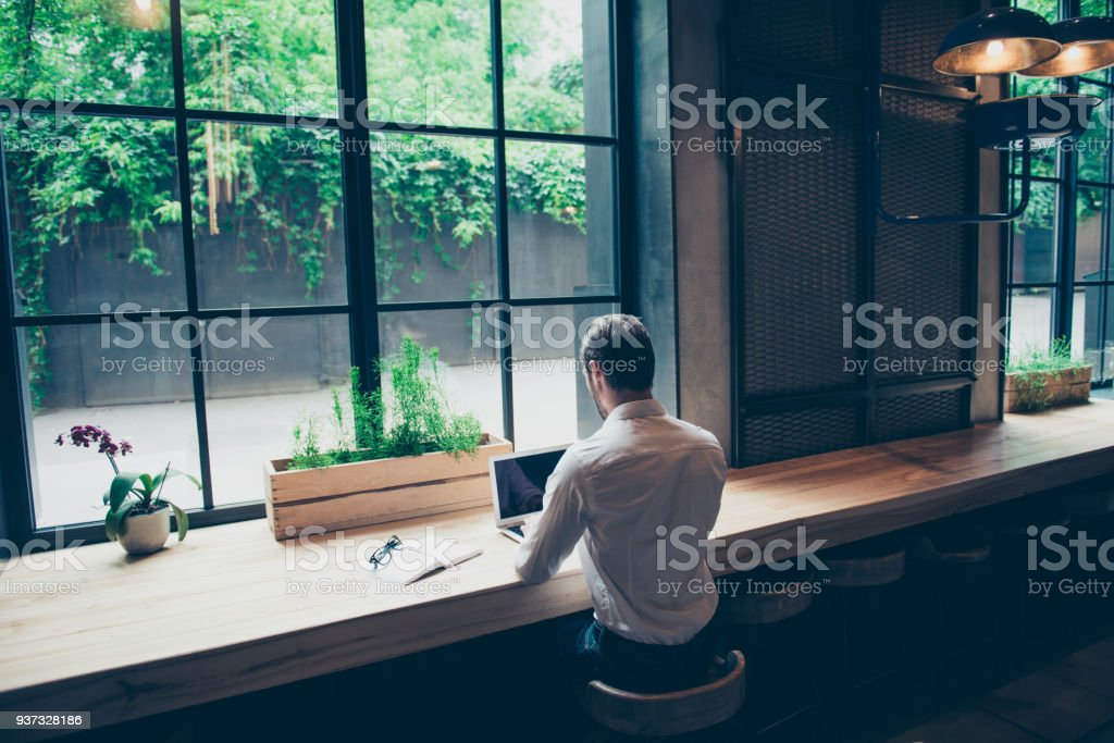 Rear view of a journalist stylish guy writing a story in a workplace in loft styled coworking, well dressed, sitting near window with view of garden stock photo