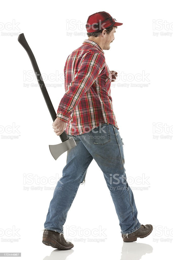 Rear view of a lumberman walking with an axe royalty-free stock photo