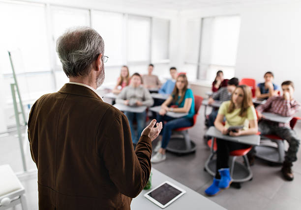 rear view of a male teacher giving a lecture. - professor stock photos and pictures