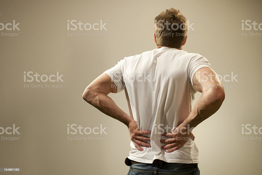 Rear view of a man in t-shirt holding his back in pain. stock photo