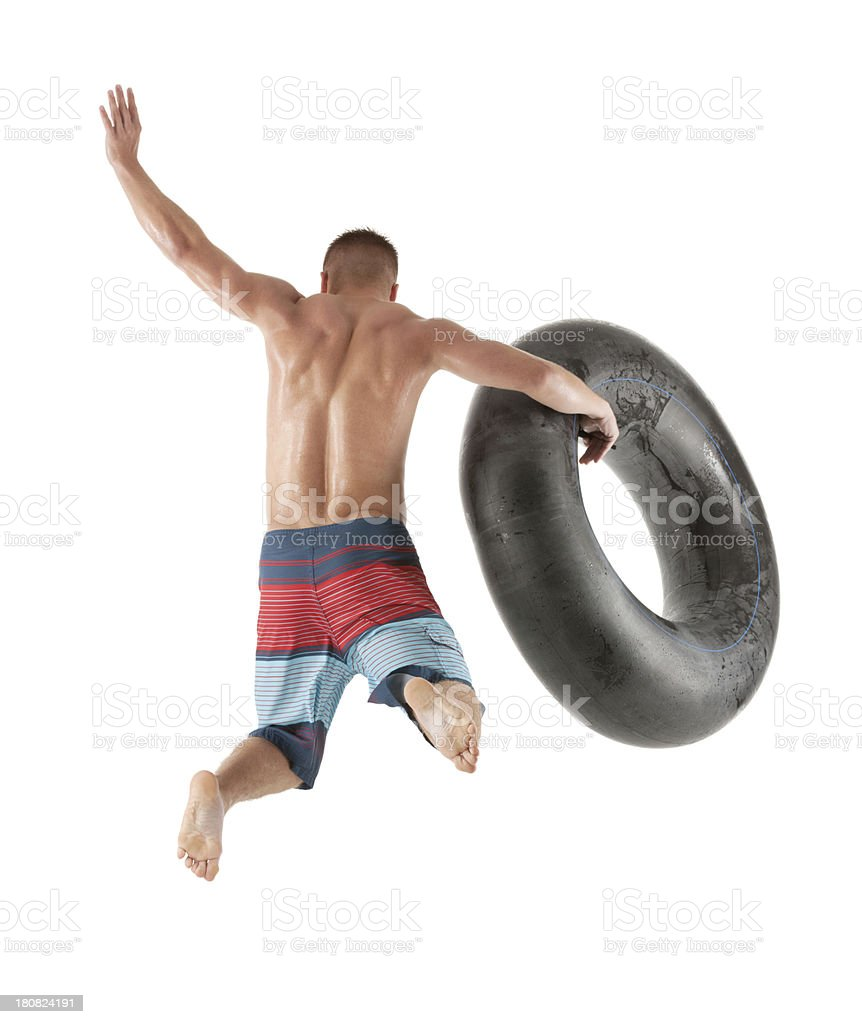 Rear view of a man jumping with an inner tube royalty-free stock photo