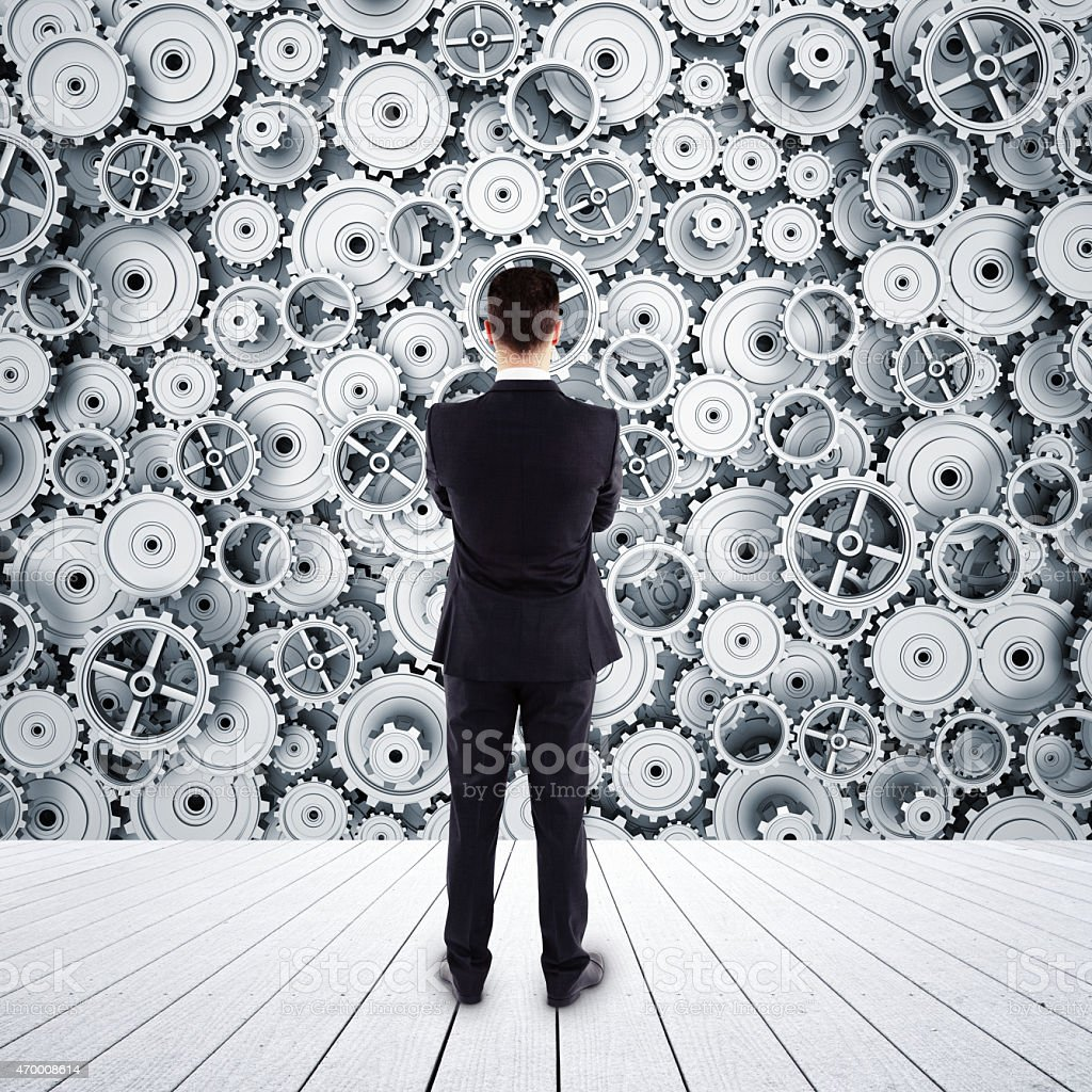 A rear view of a man looking at gears stock photo