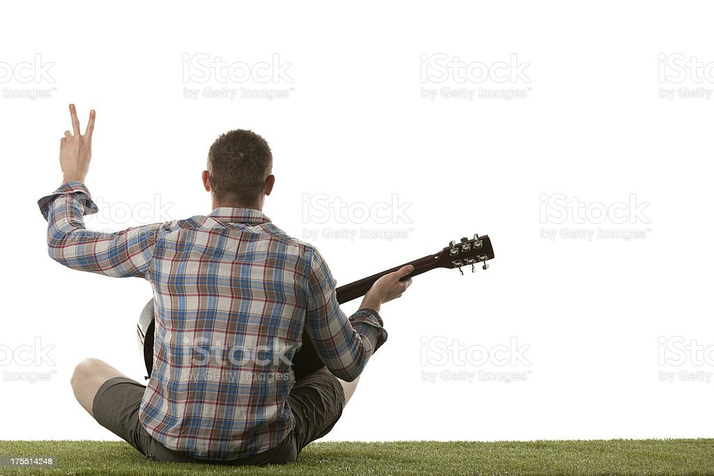 Rear view of a man playing guitar and showing 'V' stock photo