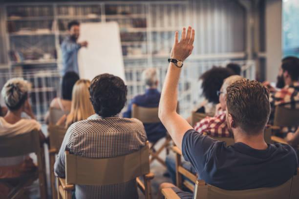Rear view of a man raising his arm on a seminar. stock photo