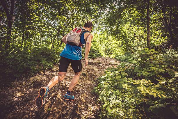 vista posterior de un hombre corriendo en el bosque arriba - trail running fotografías e imágenes de stock