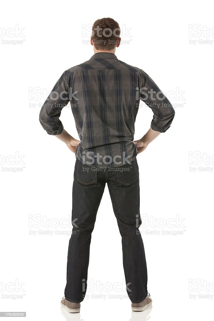 Rear view of a man standing with his arms akimbo royalty-free stock photo