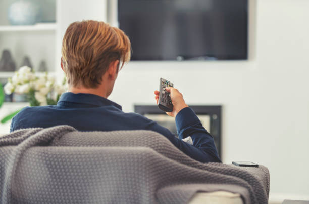 Rear view of a man watching television. Rear view of a man watching television. He is sitting on a sofa and the TV can be seen in the background. He is holding a remote control. cable tv stock pictures, royalty-free photos & images