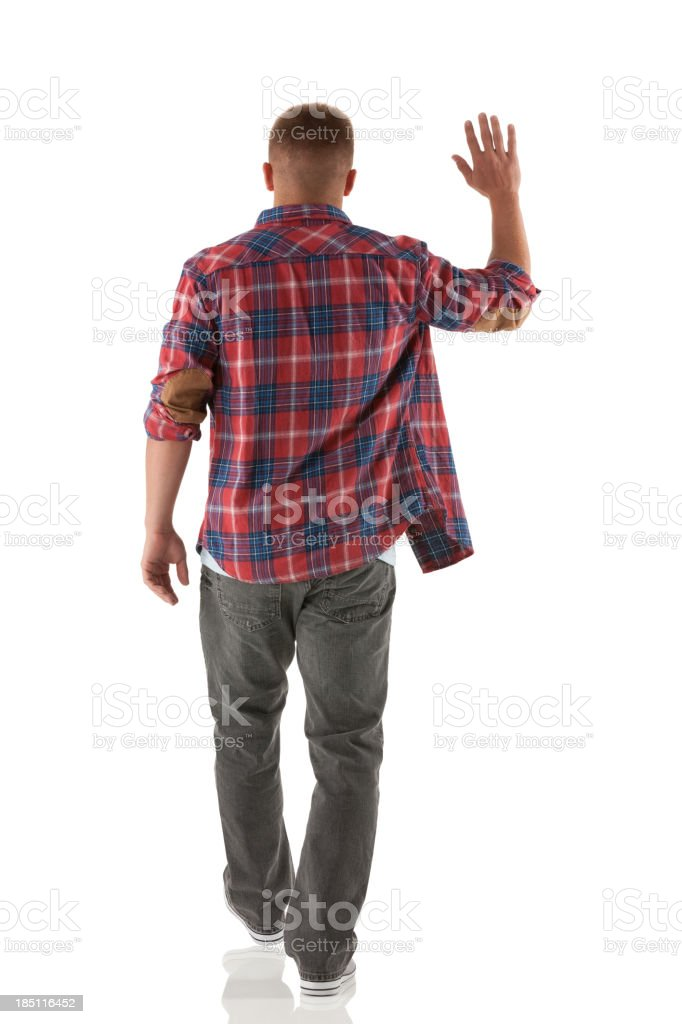 Rear view of a man waving hands stock photo