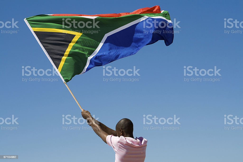 Rear view of a man waving South African flag in clear sky stock photo