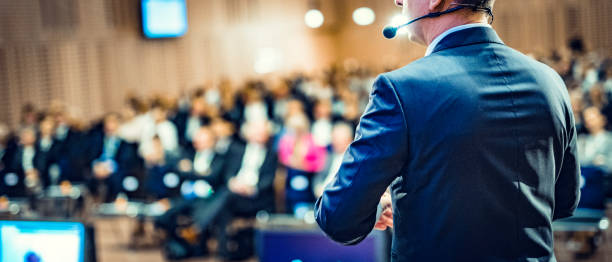 Rear view of a motivational coach giving a speech Rear view of a businessman entrepreneur giving a lecture to a sold-out crowd in a lecture hall. event stock pictures, royalty-free photos & images