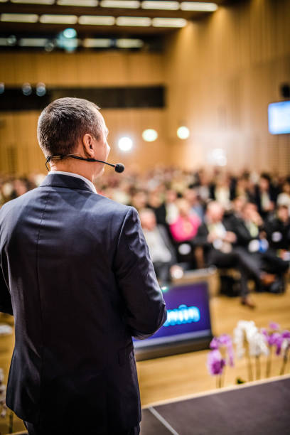 Rear view of a motivational coach giving a speech Rear view of a businessman entrepreneur giving a lecture to a sold-out crowd in a lecture hall. presenter stock pictures, royalty-free photos & images