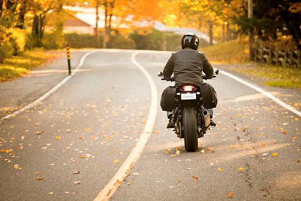 rear view of a motorcycle rider on the highway - biker stock photos and pictures