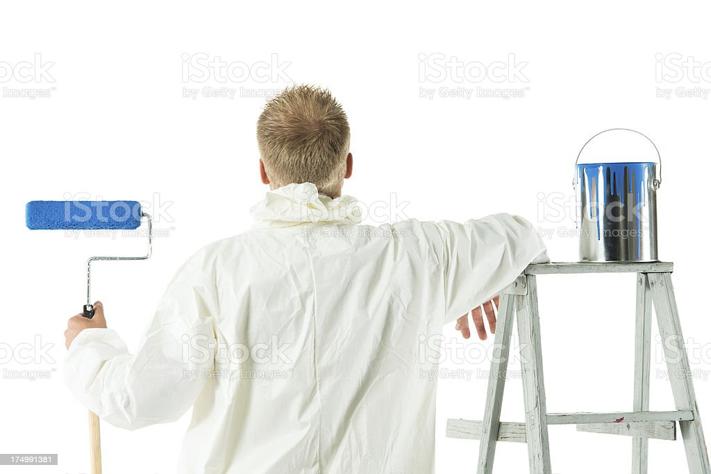 Rear view of a painter with paint roller stock photo
