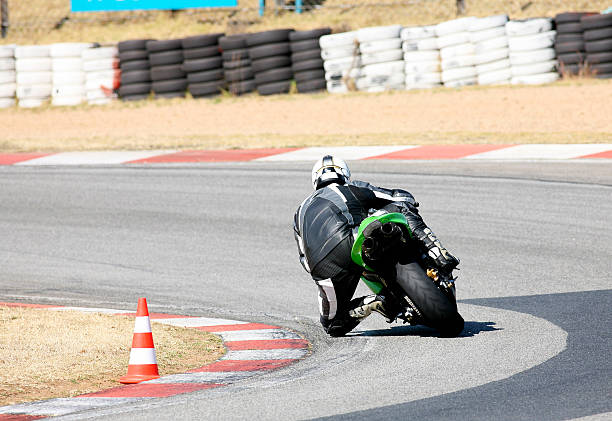 Rear view of a person on a superbike rounding a sharp curve stock photo