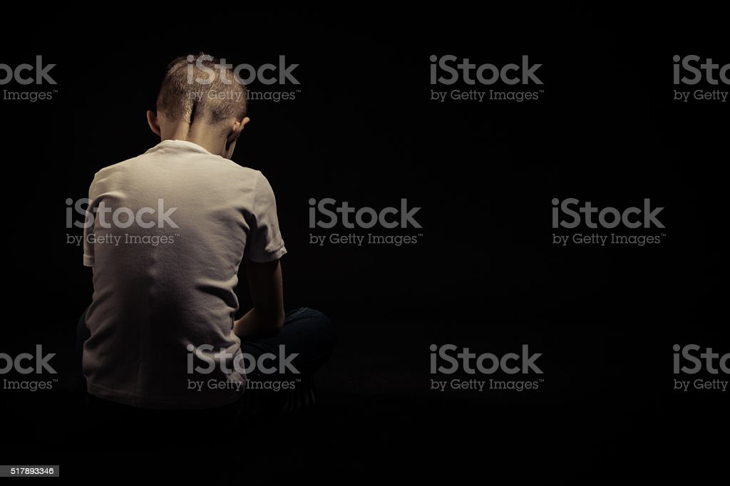 Rear View of a Seated Sad Young Boy Against Black stock photo