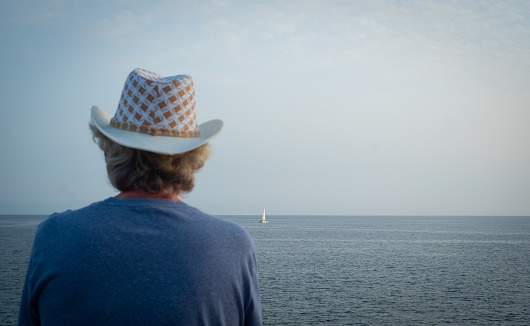 Rear view of a senior caucasian man looking at the horizon over water. Seascape of the atlantic ocean. Blue sky at sunset.