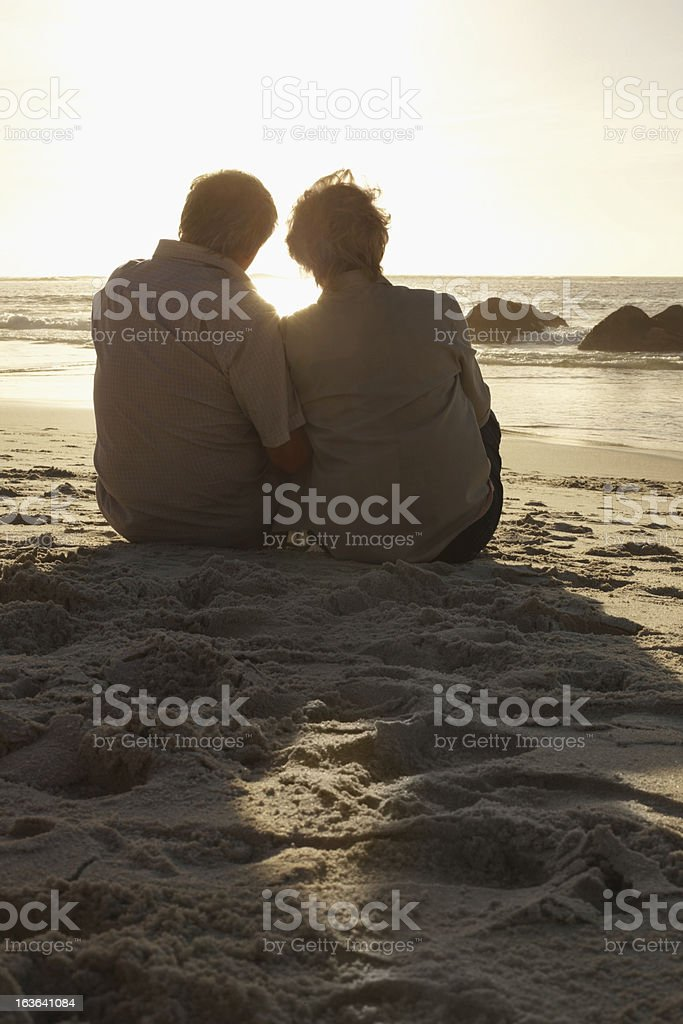 Rear view of a senior couple sitting together on beach royalty-free stock photo