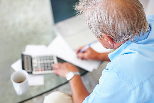 Rückansicht eines älteren Mannes rechnen finanziellen Budgets – Foto