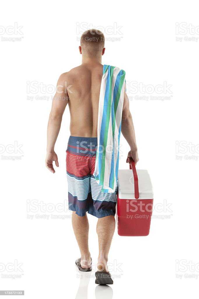 Rear view of a shirtless man walking with cooler royalty-free stock photo