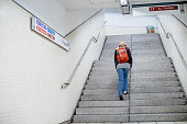 Barcelona, Spain - Nov 14, 2017: rear view of a single woman rising staircase in Barcelona MOtro Station with destination L7 Av Tibidabo