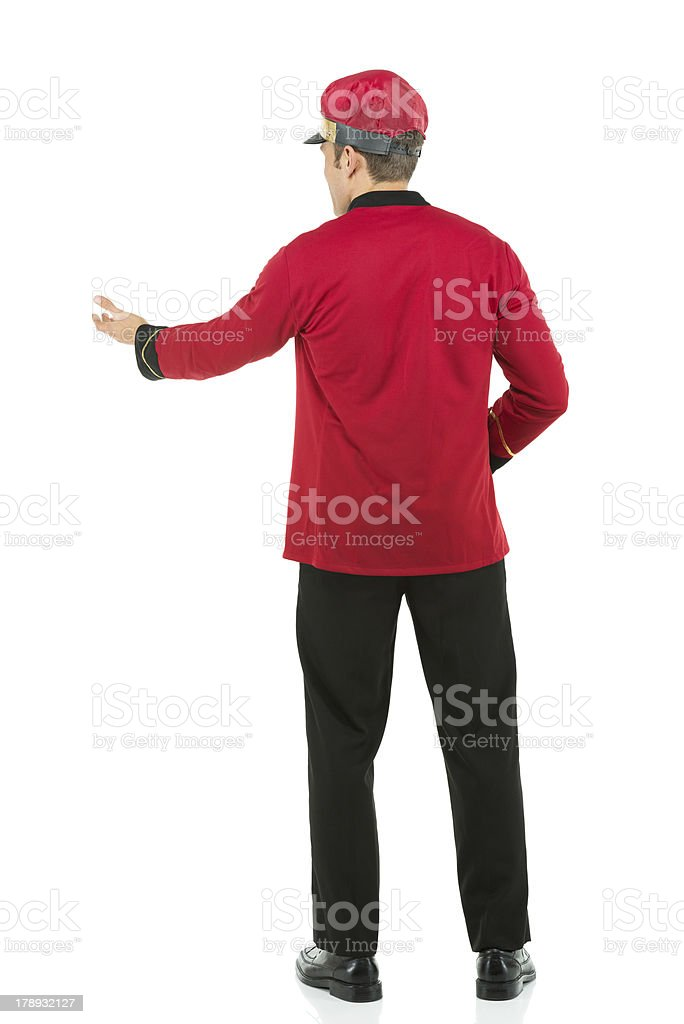 Rear view of a valet gesturing stock photo