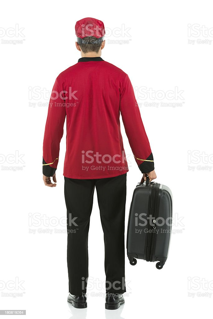 Rear view of a valet standing with suitcase royalty-free stock photo