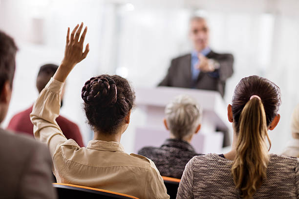 Rear view of a woman asking a question on seminar. Back view of a businesswoman raising her hand on education event. She wants to ask something. attending stock pictures, royalty-free photos & images