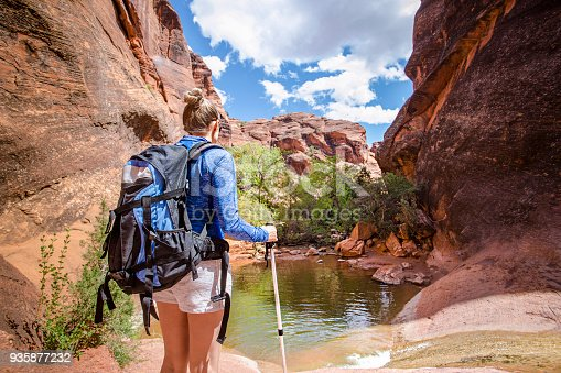 Rear view of a Woman hiking to a waterfall in a red rock canyon. She is experiencing desert beauty in the United States. Looking down at this natural water slide in a slot canyon