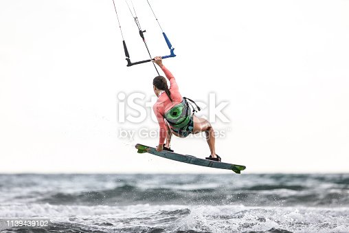 Back view of a woman having fun while jumping with kiteboard during summer day at sea.