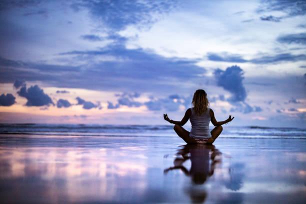 vista traseira de uma mulher que medita durante a noite na praia. - meditation - fotografias e filmes do acervo