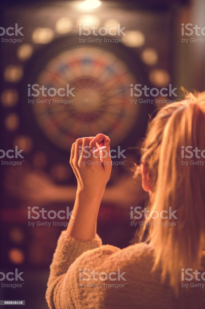 Rear view of a woman playing darts in entertainment club. stock photo
