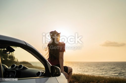 Rear view of a woman sitting in a car looking at view