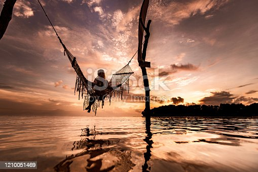 Back view of carefree woman relaxing in hammock above the sea. Copy space.