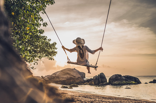 Rear view of a woman swinging during summer vacation on a beach.